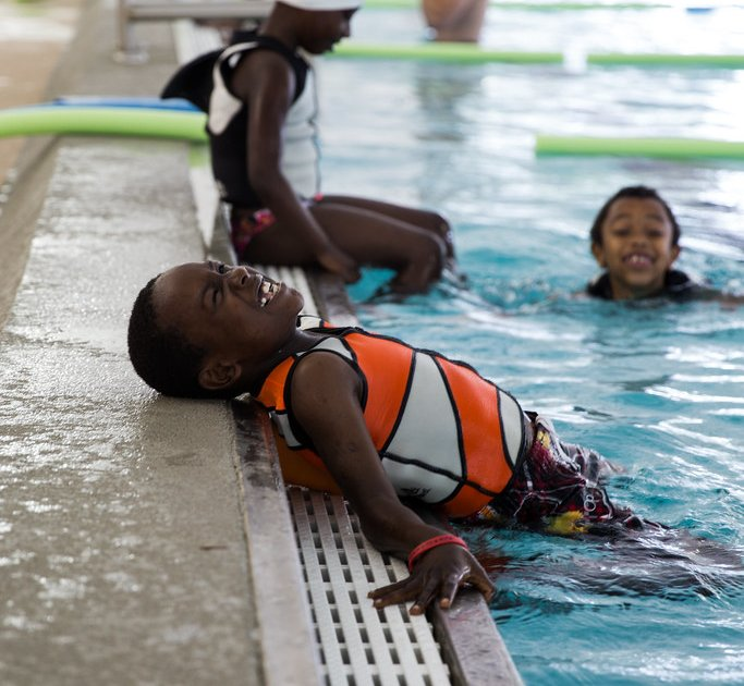A boy smiling in a swimming pool